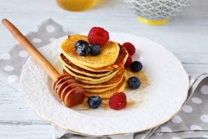 Pancakes with blueberries and honey on a plate